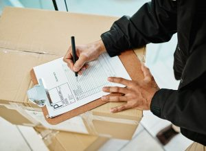 High angle shot of a courier using a clipboard while sorting boxes for delivery